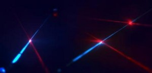 An artist's impression of distributed qubits (the bright spots) linked to each other via photons (the light beams). The colors of the beams represent that the optical frequency of the photons in each link can be tailored to the needs of the network. (Credit: Mete Atature)