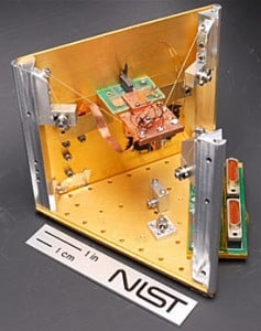 NIST's prototype solid-state refrigerator uses quantum physics in the square chip mounted on the green circuit board to cool the much larger copper platform (in the middle of the photo) below standard cryogenic temperatures. Other objects can also be attached to the platform for cooling. Credit: Schmidt/NIST