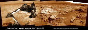Curiosity's raised robotic arm and drill are staring at you in this new panoramic vista of Yellowknife Bay basin snapped on March 23, Sol 223, by the rover's navigation camera system. The raw images were stitched by Marco Di Lorenzo and Ken Kremer and colorized. Credit: NASA/JPL-Caltech/Marco Di Lorenzo/KenKremer (kenkremer.com)