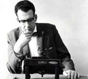 Maarten Schmidt used this microscope to examine quasar spectra. The photo was taken after his 1965 discovery of five quasars more distant than anything else then known in the universe. Credit: James McClanahan, E&S magazine, May 1965. Courtesy of the Caltech Archives