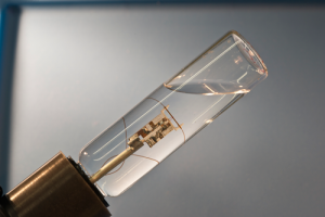 At the center of the cylinder is a microcapillary tube used to study single-particle measurement capability in magnetic contrast agents for MRI. Click on photo for enlargement of capillary and RF probe.