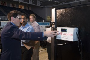 Rice senior Josh Mrozack shows the SAFE Vaccine device during the university's recent Engineering Design Showcase. The device regulates temperatures in standard refrigerators used to store vaccines and tracks their usage.