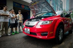 People look at an electric taxi on a street in Hong Kong, on May 18, 2013. HK saw its first electric taxis hit the streets in a step towards reducing the city's high levels of roadside pollution. The 45 bright red cars were launched by Chinese electric vehicle producer BYD, which is partly backed by US investment titan Warren Buffett.