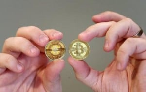 """Software engineer Mike Caldwell shows the front (R) and back (L) sides of a physical Bitcoin he minted in his shop on April 26, 2013 in Sandy, Utah. Bitcoin is an experimental digital currency used over the Internet. US authorities seized the accounts of a Bitcoin digital currency exchange operator, claiming it was functioning as an """"unlicensed money service business,"""" court documents showed."""
