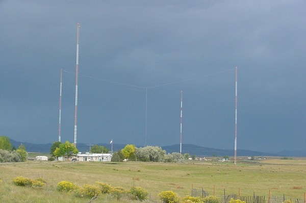Modern photo of NIST radio station WWVB. The transmitters are in the building. In the background are WWVB's four north towers supporting the antenna in the center. The cables are most visible under dark, stormy skies like this. Credit: NIST