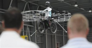 Two men watch the remote-controlled Flying Bike with a test dummy during its presentation in Prague on Wednesday, June 12, 2013. Three Czech companies have teamed up to make a prototype of an electric bicycle that can fly. Controlled remotely, the bike carrying a figurine successfully took off Wednesday inside a large exhibition hall in Prague and landed safely after a five-minute flight. (AP Photo/CTK, Stanislav Zbynek)