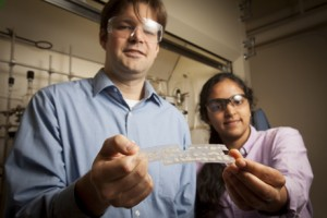 Will Dichtel, assistant professor of chemistry, and graduate student Deepti Gopalakrishnan hold samples of their polymer that uses fluorescence to detect the explosive RDX.