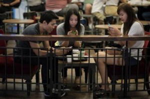A group of friends look at their smartphones at a coffee shop in Bangkok on March 19, 2013. An increasing number of options are available for those seeking to detox from technology, from wallpaper that blocks wi-fi to software that forces you off addictive sites.