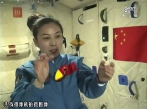 In this image taken June 20, 2013 and made from CCTV, Chinese female astronaut Wang Yaping shows motion behavior of two spinning objects in micro-gravity during the broadcast live from onboard the Tiangong 1 prototype space station. China's astronauts spun gyroscopes and implanted tiny knots into sheets of suspended water during their first classroom lecture from the country's orbiting space station, part of efforts to popularize the successful manned space flight program among young people.(AP Photo/CCTV via AP Video)