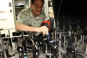 NIST physicist Alan Migdall spotlights the crystal that converts one photon to two in the middle of the complex apparatus used as a high-efficiency source of paired photon for quantum experiments. Credit: Baum/NIST