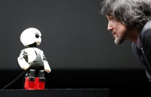 """Humanoid communication robot Kirobo, left, talks with Fuminori Kataoka, project general manager from Toyota Motor Corp., during a press unveiling in Tokyo Wednesday, June 26, 2013. The world's first space conversation experiment between a robot and humans is ready to be launched. Developers from the Kirobo project, named after """"kibo"""" or hope in Japanese and """"robot,"""" gathered to demonstrate the humanoid robot's ability to talk. Kirobo, jointly developed by advertising and PR company Dentsu Inc., Research Center for Advanced Science and Technology, the University of Tokyo, Robo Garage Co. and Toyota., is scheduled to be launched from the Tanegashima Space Center on August 4, 2013. (AP Photo/Shizuo Kambayashi)"""