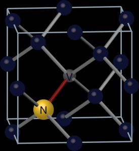 "This image represents the nitrogen-vacancy center in the atomic arrangement of diamond. The dark spheres are carbon atoms and the yellow sphere is a nitrogen atom. The ""V"" is the nitrogen-vacancy center, from which a nitrogen atom has moved to replace a nearby carbon atom. Teams led by the University of Chicago's David Awschalom are exploiting this atomic defect to develop new quantum technologies. Credit: Peter Allen"