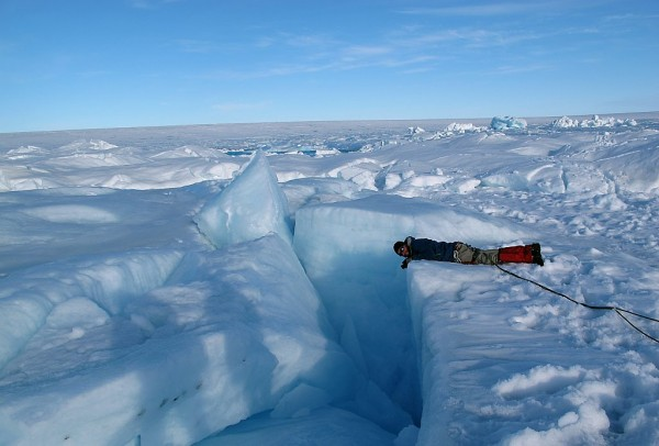 Researcher Marco Tedesco peers into a crevasse on the Greenland ice sheet. Credit: Marco Tedesco, NSF