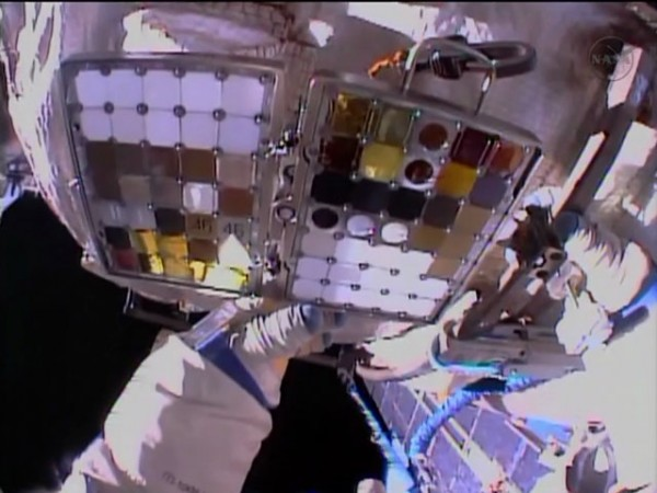 Flight Engineer Alexander Misurkin takes a look at a materials exposure experiment during an Expedition 36 spacewalk. Image Credit: NASA TV