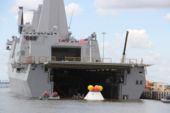 During the stationary recovery test of Orion at Norfolk Naval Base on Aug. 15, 2013, US Navy divers attached tow lines and led the test capsule to a flooded well deck on the USS Arlington. Credit: Ken Kremer