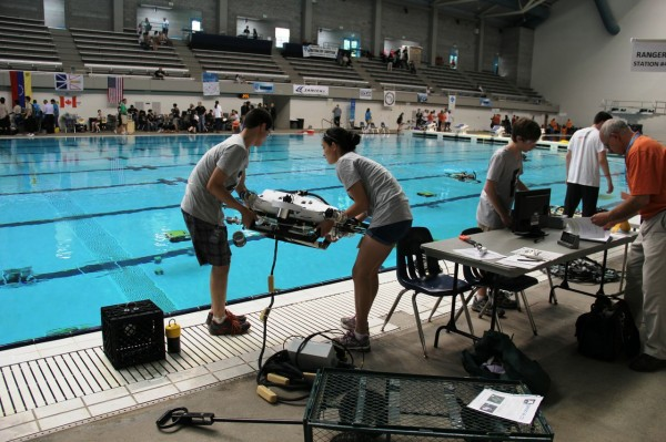 Team members move their vehicle from their mission table to the pool deck as they prepare to launch it. Credit: MATE Center