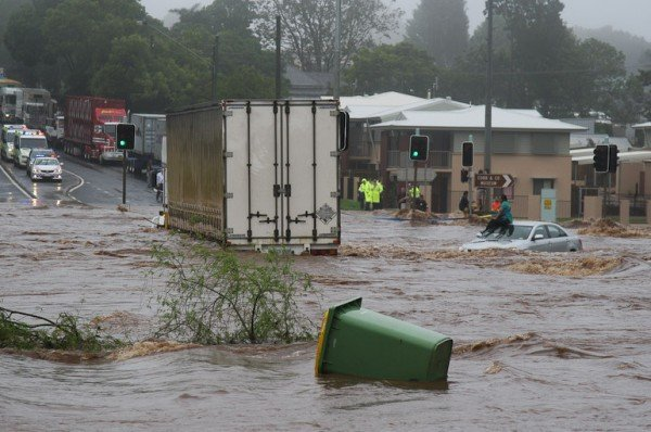 A woman in Australia awaits rescue on a car roof. Credit: Government of Australia
