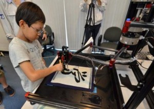 "A boy writes a Chinese letter for ""study"" with a calligraphy robot at Keio University in Yokohama on July 30, 2013. The motion copy robot can recreate master works and the users can experience the same pressure and the same gestures of brush works by master painters or calligraphers."