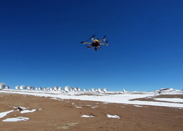 This strange looking contraption is a hexacopter, installed with a camera, which can be used for radio-controlled aerial cinematography and photography. In the background the Atacama Large Millimeter/submillimeter Array (ALMA) sprawls out across the Chajnantor Plateau in Chile soon to be photographed from above. Credit: ALMA (ESO/NAOJ/NRAO)