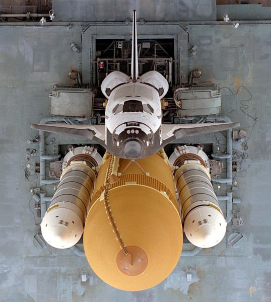 Atlantis begins the slow journey to Launch Pad 39A from the Vehicle Assembly Building (VAB) in preparation for the launch of STS-79 in 16 September 1996. This dramatic view looking directly down onto the shuttle stack atop the Mobile Launcher Platform (MLP) and crawler-transporter was taken from the VAB roof approximately 525 feet (160 meters) above the ground. In view are the Orbiter, orange External Tank and twin white Solid Rocket Boosters. Credit: NASA