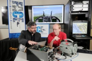 Douglas Woods, left, a research scientist leading the Future Airborne Capability Environment (FACE) project for the Georgia Tech Research Institute (GTRI), discusses the technology with research-team member George Riley, a professor in the School of Electrical and Computer Engineering. (Georgia Tech Photo: Gary Meek)