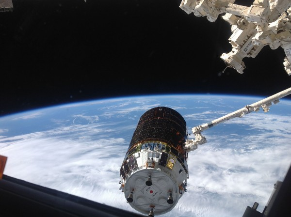 """The International Space Station's Canadarm2 grapples the unpiloted Japanese """"Kounotori"""" H-II Transfer Vehicle-4 (HTV-4) as it approaches the station. Image Credit: NASA"""