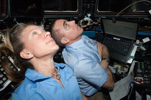 """NASA astronauts Karen Nyberg and Chris Cassidy, both Expedition 36 flight engineers, are pictured at the robotic workstation in the Cupola of the International Space Station during rendezvous operations with the approaching unpiloted Japanese """"Kounotori"""" H2 Transfer Vehicle-4 (HTV-4). Image Credit: NASA"""