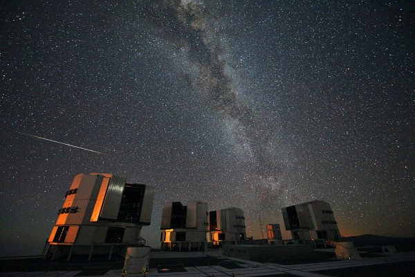 A Perseid meteor (at left) seen in August 2010 above the four enclosures of the European Southern Observatory's Very Large Telescope at Paranal, Chile. Credit: ESO / S. Guisard.