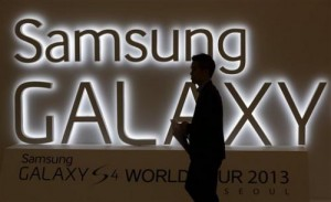 In this photo taken on April 25, 2013, a man walks by a logo of Samsung Electronics Co.'s latest smartphone Galaxy S4 during its unveiling ceremony in Seoul, South Korea. Samsung Electronics Co. has applied for U.S. and South Korean trademarks for a watch that connects to the Internet in the latest sign that consumer technology companies see wearable devices as the future of their business. (AP Photo/Lee Jin-man)