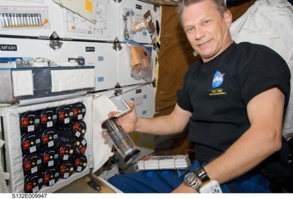 STS-132 mission specialist Piers Sellers handles the group activation packs aboard space shuttle Atlantis. Image Credit: NASA