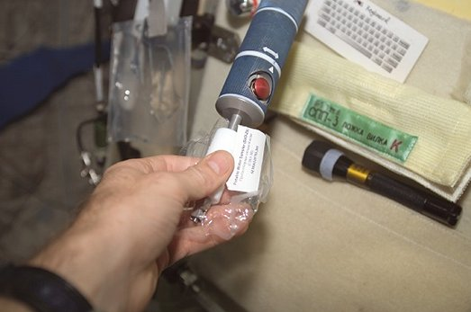 Expedition 8 Commander Michael Foale holds a sample bag to the nozzle of the potable water dispenser at the galley in the Zvezda Service Module as part of Crew Healthcare System (CHeCS) in-flight analysis sampling. Image Credit: NASA