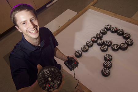 Postdoctoral researcher Aaron Becker designed a new control algorithm that allows swarms of r-one robots from Rice's Multi-Robot Systems Laboratory to complete complex tasks -- including spelling out Rice's trademark R.