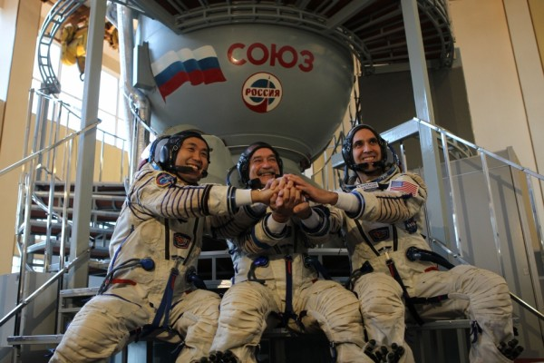 Left to right: Expedition 38 Flight Engineer Koichi Wakata, Soyuz Commander Mikhail Tyurin and NASA Flight Engineer Rick Mastracchio clasp hands in front of a Soyuz simulator during final qualification exams ahead of their Nov. 7 launch to the space station. Image Credit: NASA
