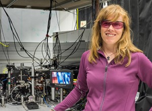 NIST physicist Elizabeth Donley with a compact atomic clock design that could help improve precision in ultraportable clocks. About 1 million cold rubidium atoms are held in a vacuum chamber in the lower left of the photo. On the screen is a close-up of the atom trapping region of the apparatus. Credit: vonDauster/NIST