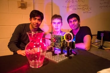 "MIT students (left to right) Ayush Bhandari, Refael Whyte and Achuta Kadambi pose next to their ""nano-camera"" that can capture translucent objects, such as a glass vase, in 3-D. Photo: Bryce Vickmark"