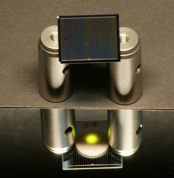 A two-sided silicon solar cell – positioned here on aluminum cylinders – is illuminated from above by an infrared laser. © Fraunhofer ISE