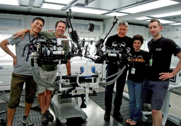 On the movie set with the University of Washington's Raven II surgical robot. From left to right: Hawkeye King, director Gavin Hood, Harrison Ford, robotics expert Joanne Pransky and Lee White. Credit: UW