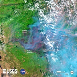 A recent image from the Landsat 8 satellite in the vicinity of Yosemite National Park, California, during the Rim Fire (August 31). Started on August 17, the Rim Fire had burned over 219,000 acres by August 31 (an area nearly 15 times the size of Manhattan Island). Image is false-colored using bands 6, 5, 4 to allow identification of critical vegetation and fuels information that will help firefighters and emergency managers. In the image fire appears bright red, vegetation is green, smoke is blue, clouds are white, and bare ground is tan-colored.