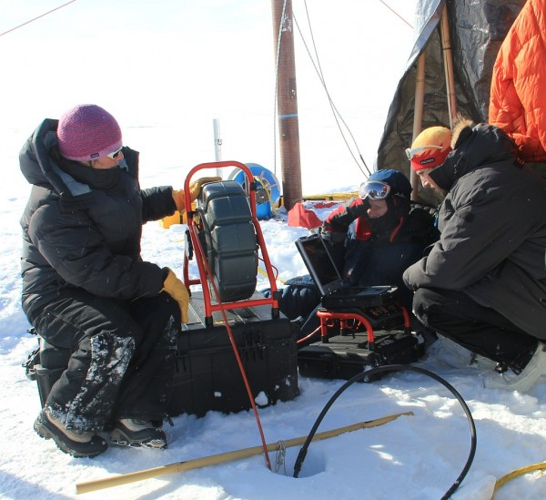 Glaciologist Lora Koenig (left) operates a video recorder that has been lowered into the bore hole to observe the ice structure of the aquifer in April 2013. Image Credit: University of Utah/Clément Miège