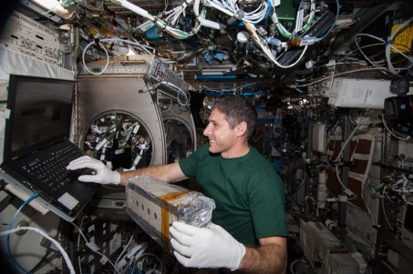 Aboard the International Space Station, astronaut Mike Hopkins works with a cell array for the Selectable Optics Diagnostic Instrument-Diffusion Coefficient in Mixtures 2 (SODI-DCMIX 2) investigation. Findings may help refine petroleum reservoir models for more efficient extraction of oil resources. Image Credit: NASA