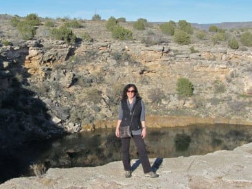 Ingram stands in front of an Arizona sinkhole known as the Montezuma Well. It served as a water source for the Sinagua people until they disappeared from the area around AD 1300.
