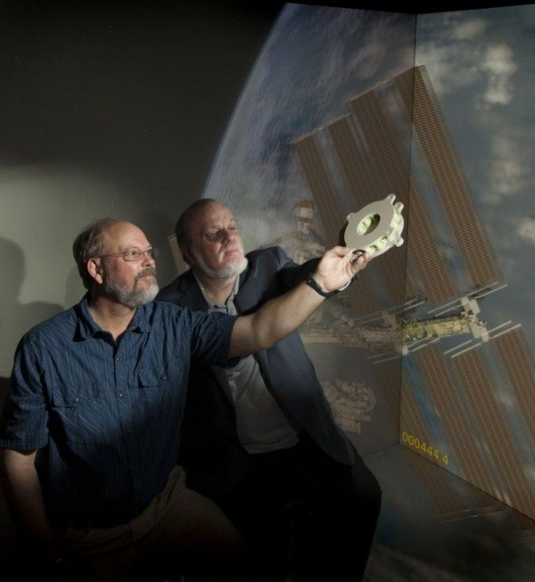 Goddard technologists Ted Swanson and Matthew Showalter hold a 3-D-printed battery-mounting plate developed specifically for a sounding-rocket mission. The component is the first additive-manufactured device Goddard has flown in space. Image Credit: NASA