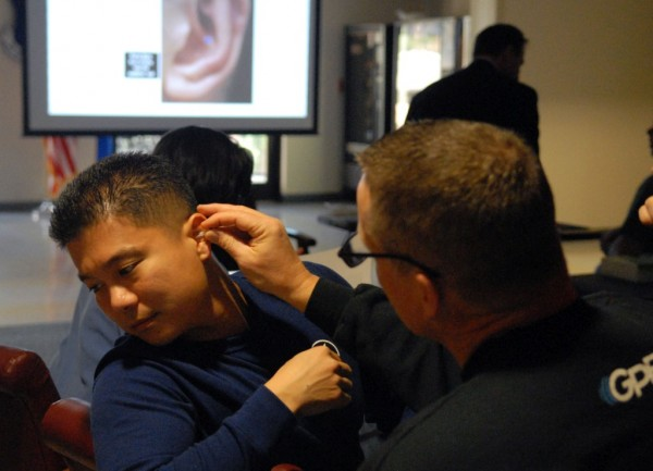 Capt. Yusharn Wang (left), Family Health Nurse Practitioner, and Col. Daniel Weaver, acting Chief of Medical Services, both from the 78th Medical Group, practice Auricular Therapy Acupuncture, March 1, 2014. The human ear has many points that relieve headaches and muscle pains all over the body. (U.S. Air Force photo/Misuzu Allen)