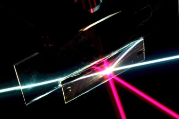 n this photo of the angular-selective sample (the rectangular region), a beam of white light passes through as if the sample was transparent glass. The red beam, coming in at a different angle, is reflected away, as if the sample was a mirror. The other lines are reflections of the beams. (This setup is immersed in liquid filled with light-scattering particles to make the rays visible). Photo: Weishun Xu and Yuhao Zhang