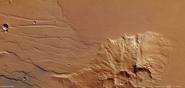 Two distinct volcanic eruptions have flooded this area of Daedalia Planum on Mars, flowing around an island of ancient terrain. The smooth, fractured terrain to the south (left) predates the rough-textured lava flow that dominates the northern (right) side of the image. The lava flows arose from the giant Arsia Mons volcano, part of the Tharsis complex around 1000 km to the northwest. The blue–grey colour at the bottom left of the image likely reflects a difference in the composition of exposed material: for example, wind-blown ash or dust deposits can easily accumulate in faults or channels. The image was created using data acquired on 28 November 2013 during Mars Express orbit 12 593 using the High Resolution Stereo Camera. The image resolution is about 14 m per pixel. The image centre is at about 25ºS/249ºE. North is right and east down. Copyright ESA/DLR/FU Berlin