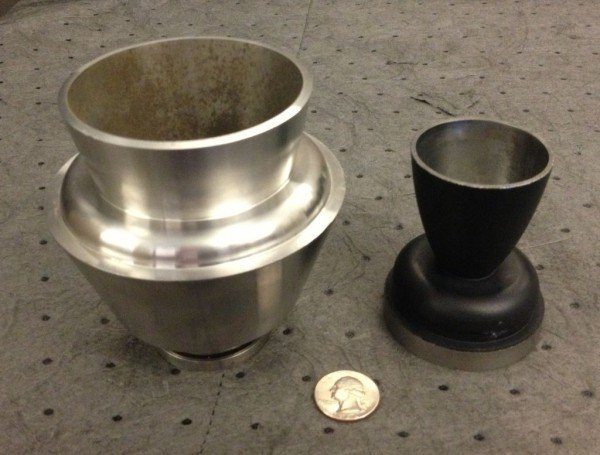 A size comparison of the booster and engine nozzles to a quarter. Image Credit: NASA/MSFC