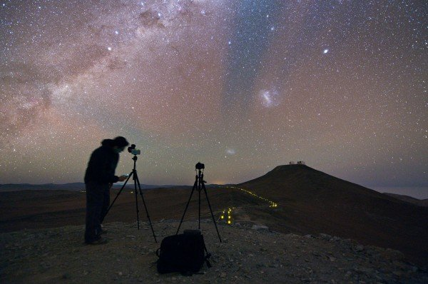 Action shot of the Ultra HD Expedition member Babak Tafreshi as he prepares his camera to capture the glittering canvas of the night sky. The red and green glow in the sky is due to airglow in the upper atmosphere. Credit: ESO/Y. Beletsky