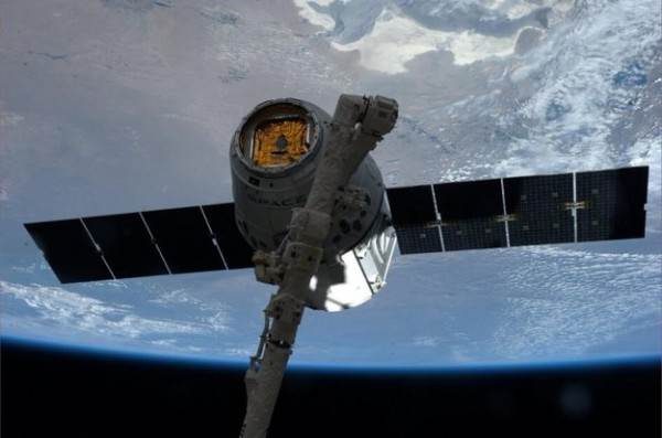 Dragon CRS-3 space ferry as it is captured by the International Space Station's robotic arm. The spacecraft was launched from Cape Canaveral, USA, on 18 April 2014. It arrived at the Station two days later with over two tonnes of equipment, supplies and scientific experiments. Stowed in Dragon's cargo are lentil seeds that will be nurtured into life on the International Space Station as part of the Gravi-2 experiment investigating how sensitive plants are to gravity. Copyright NASA