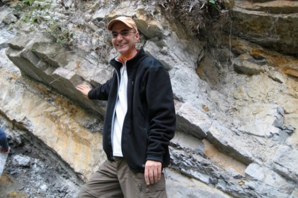 MIT professor of geophysics Daniel Rothman stands next to part of the Xiakou formation in China. His right hand rests on the layer that marks the time of the end-Permian mass extinction event. Samples from this formation provided evidence for large amounts of nickel that were spewed from volcanic activity at this time, 252 million years ago. Photo courtesy of Daniel Rothman