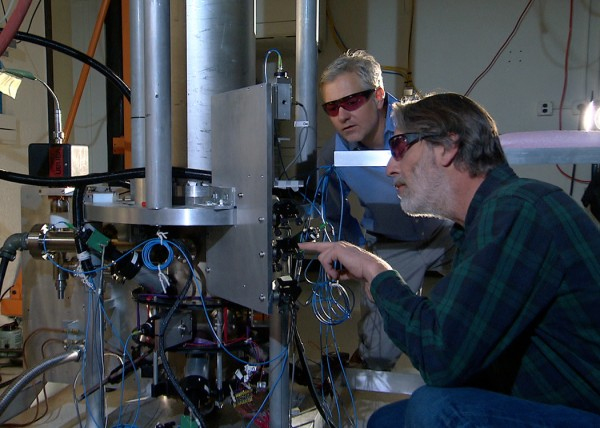 """NIST physicists Steve Jefferts (foreground) and Tom Heavner with the NIST-F2 """"cesium fountain"""" atomic clock, a new civilian time standard for the United States. Credit: NIST"""